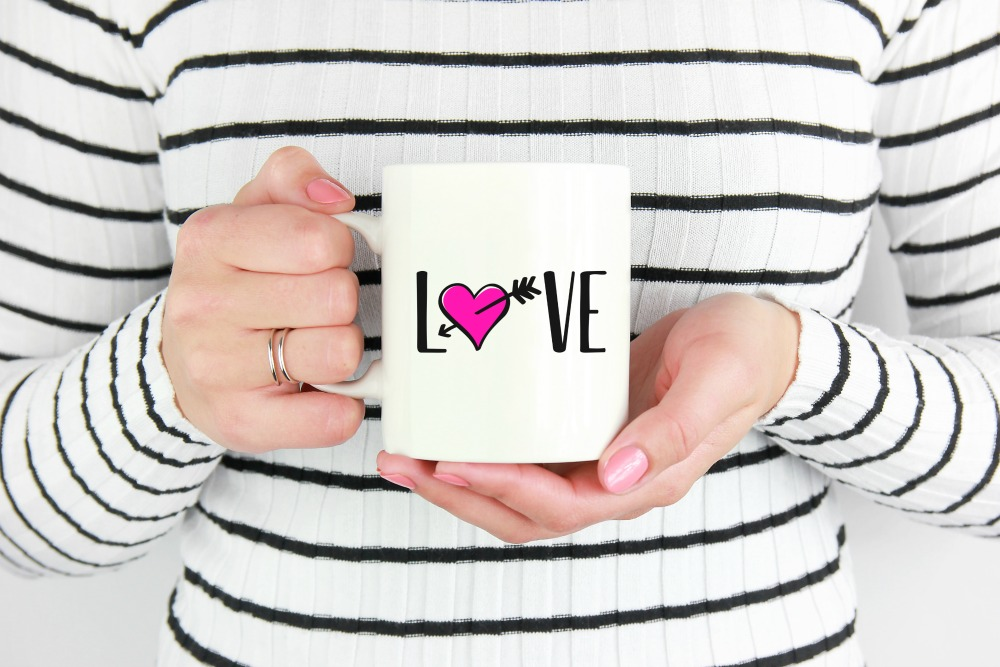 Create a cute custom mug for Valentines Day, or wedding shower favors using your Cricut or Silhouette cutting machine and Hello Creative Familys free Love SVG File! A fun and easy craft project! #SVG #Cricut #Silhouette #Crafts