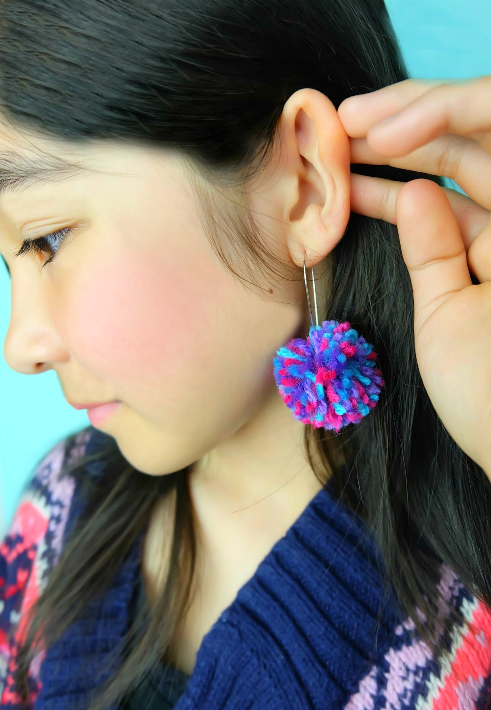 Learn how to make DIY Pom Pom Earrings in minutes with this quick and easy tutorial! Make an adorable pair of earrings to match any outfit! Also learn how to make a DIY pom pom maker in any size using a piece of cardboard! This would make an adorable handmade gift for teens or tweens! #DIY #Craft #pompoms #Earrings