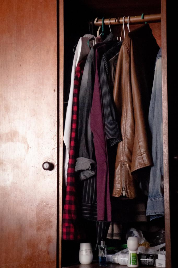 brown wardrobe with hanging with casual clothes on hangers