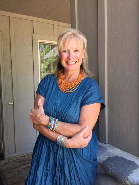 Robin LaMonte is wearing a fabulous blue bohobchic dress and orange multistrand necklace