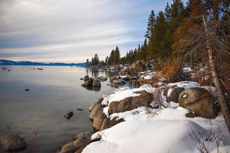 Zephyr Cove in South Lake Tahoe. Snow over rocks on edge of lake.
