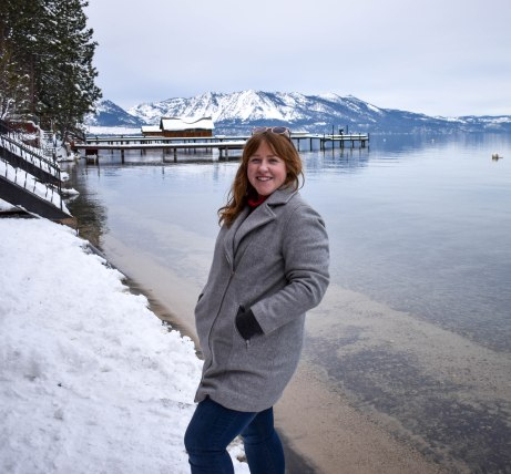 El Dorado Beach, South Lake Tahoe. Woman on grey coat, standing on edge of lake.