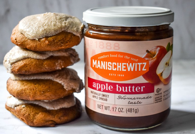 Stack of dairy free apple butter cookies with vanilla and cinnamon icing next to a jar of manischewitz apple butter. a white marbled background.