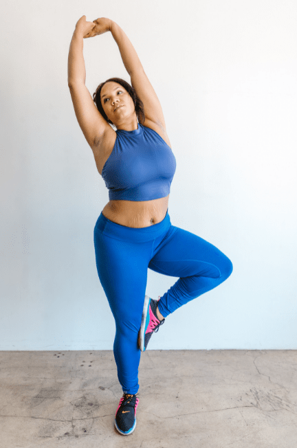 A woman doing a yoga pose in a blue yoga outfit.