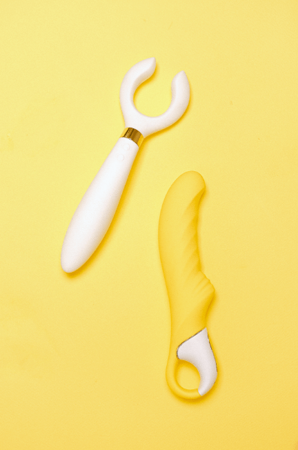 One white, one yellow and white sex toy against a yellow background