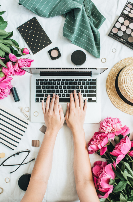 Hands typing on a macbook surrounded by pink flowers, a hat, glasses a note pad a few pieces of makeup