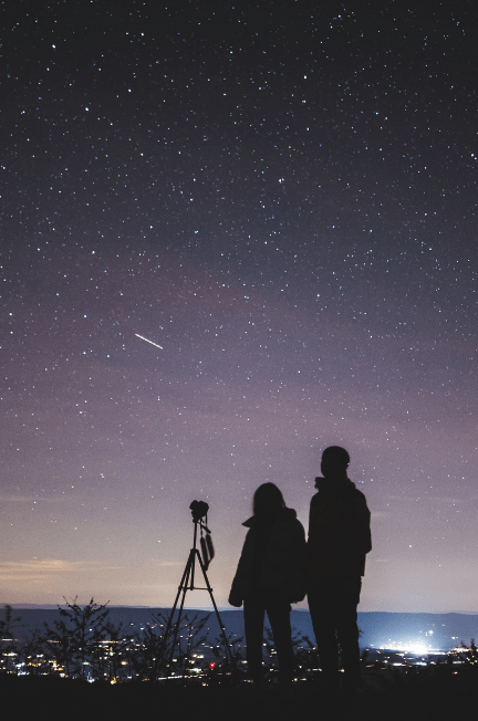 Two people standing by a telescope overlooking the city lights and the night sky