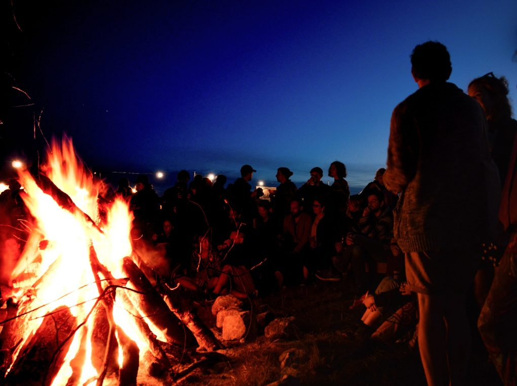 crowd around a campfire on the beach