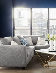 Living room furniture ideas: A large grey sectional with chaise is beautifully lit in a living room with mixed metal decor accessories.