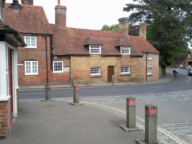 The road through Beaulieu village with red brick cottages.  Wooden bollards display the fusils of the Montagu coat of arms