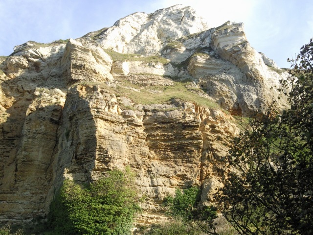 A rugged white cliff seen from below