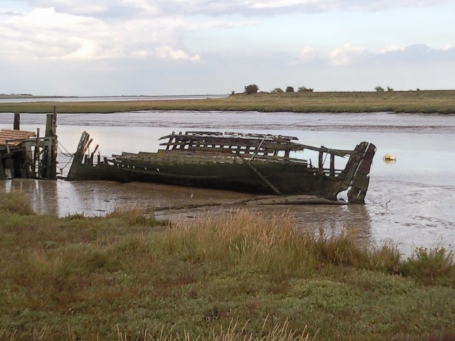 An abandoned boat decaying beside Faversham Creek