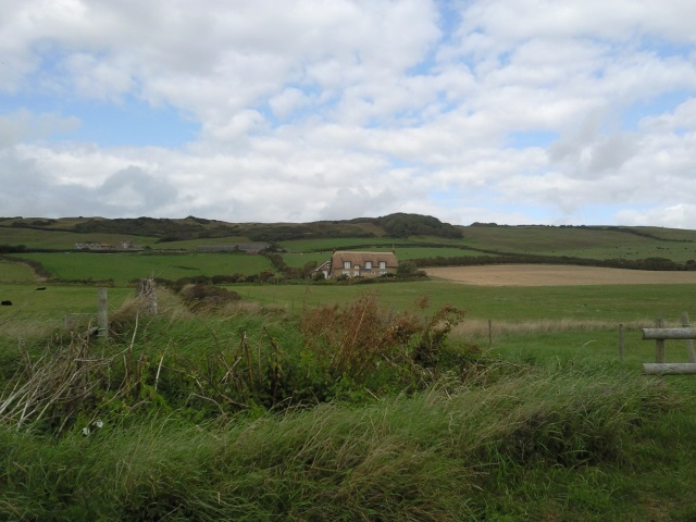 A large farm cottage, surrounded by open fields and set back some distance from the road