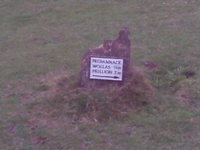 SIgn on a rock, pointing to Predannack Wollas and Mullion