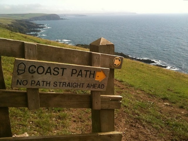 A sign for the coast path pointing down the steep coastal slope.