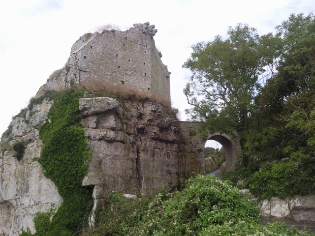 A ruined castle on a rocky stack, accessed only via an arched bridge