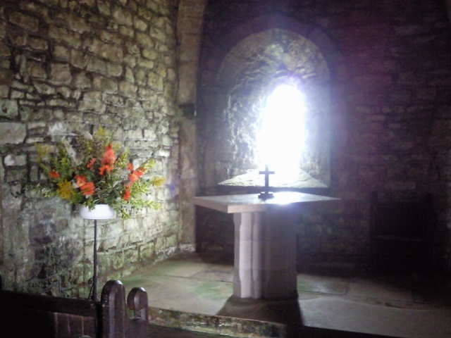 Chapel interior with stone walls, an altar and a display of flowers. Light is glaring through a window behind.