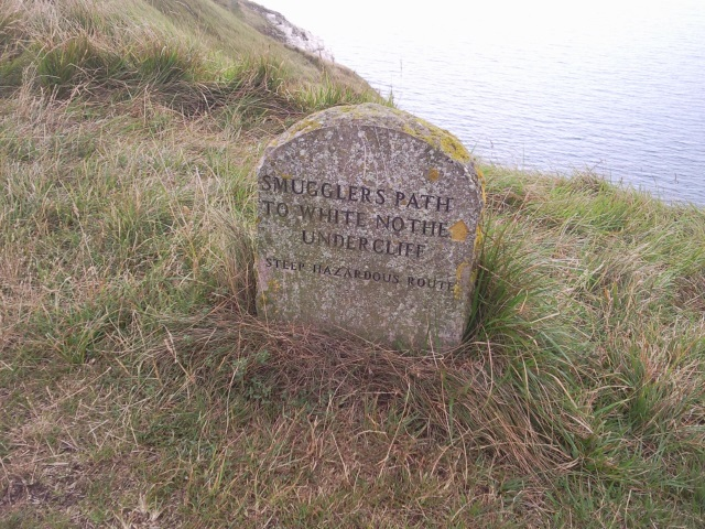 Stone marker with inscription: Smugglers' Path to White Nothe Undercliff. Steep hazardous route.