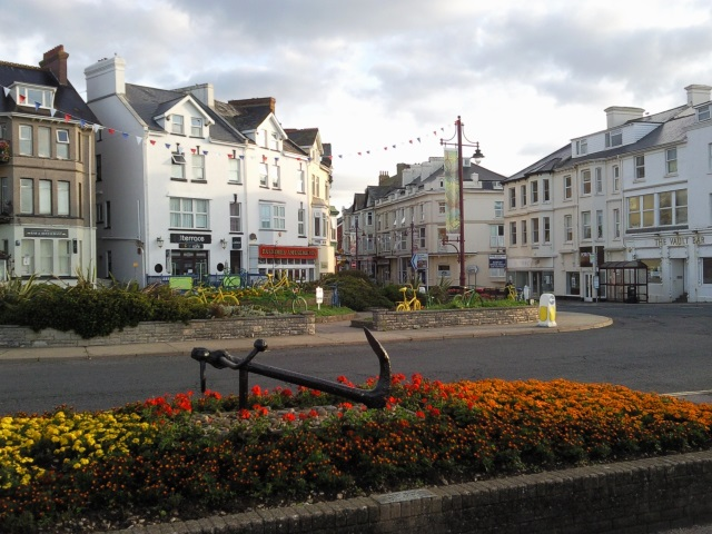 A street in Seaton near the seafront. Flowerbeds on a roundabout contain brightly-coloured bicycles as some sort of civic art installation.