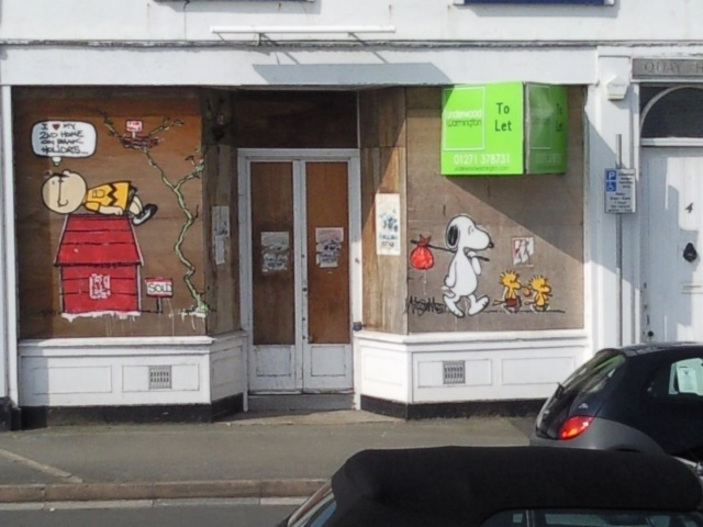 A boarded-up shop with a home-made Charlie Brown cartoon: 'I love my second home on bank holidays,' thinks Charlie Brown as Snoopy and Woodstock go homeless.