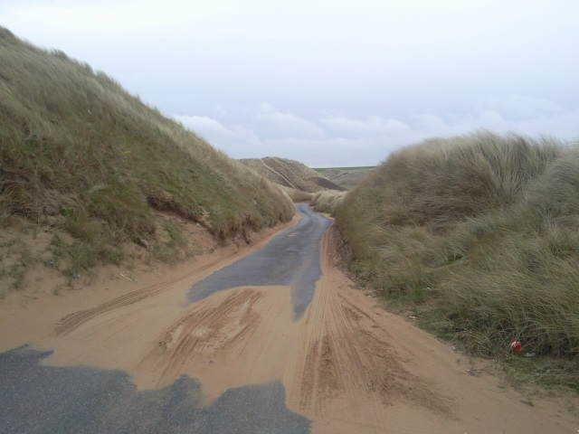Narrow road passing between sand dunes.  Some sand also lies in the road