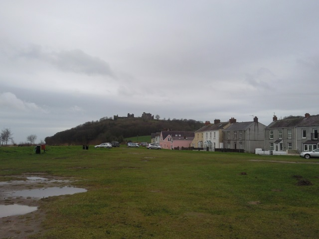 LLansteffan Castle looming over some Welsh houses