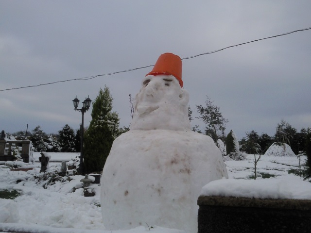 A snowman with a bucket on its head for a hat