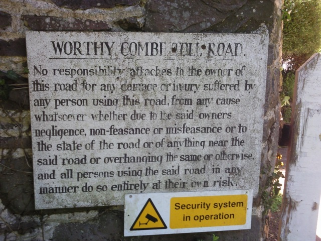 Sign: Worthy Combe Toll Road. No responsibility attaches to the owner of this road for any damage or injury...