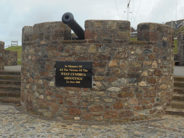 Memorial plaque for the West Cumbria Shootings mounted directly below a cannon muzzle.