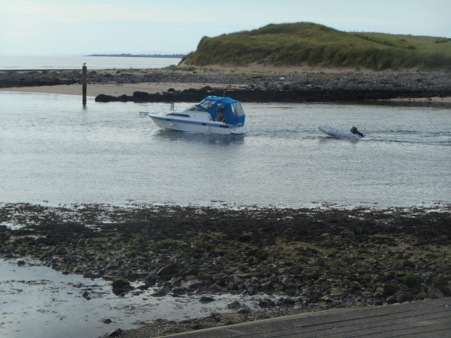 Mouth of the River Irvine. A small boat is heading out to sea.