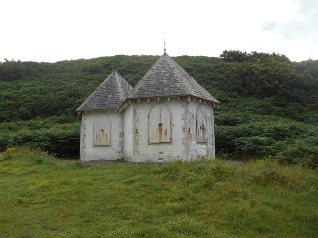A small double-hut with a pyramidal roof and arched windows (boarded-up)