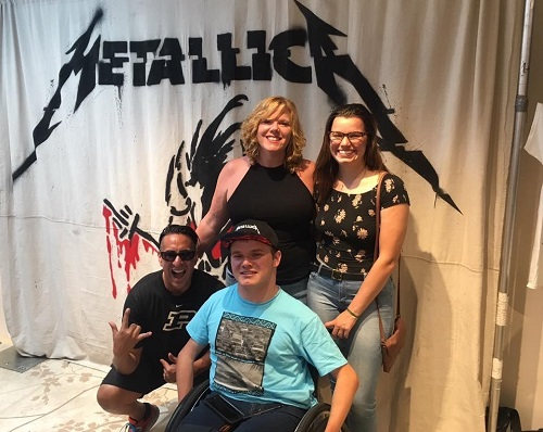 "Photo of Patrick Ivison with family and friends in front of a backdrop that says, ""Metallica""."
