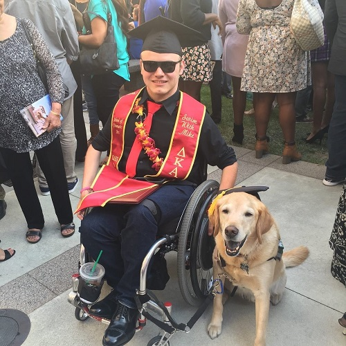Photo of Patrick Ivison at his graduation at USC, wearing graduation garb, and he is positioned next to his dog.