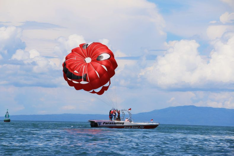 Motor boat in blue water catching skydiver with red parachute