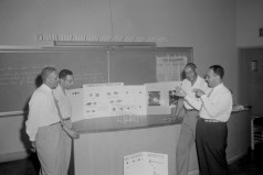 """Classroom. Unidentified men at desk in classroom with poster displays for """"Correlated Visual Aids,"""" and """"Know Your Bleaches - Antiseptics,"""" ca. 1947. Paul Henderson, HEN.00.B2-247."""