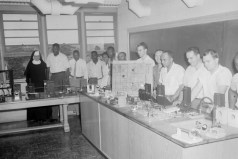 Classroom. Men and women gathered around classroom lab with equipment. Shows nun in religious habit, ca. 1957. Paul Henderson, HEN.00.B2-249.