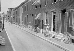 Alley houses, showing people sitting on stoops. Unidentified street, undated. Paul Henderson, HEN.00.A1-104.