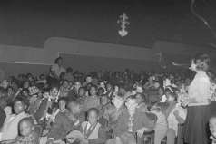 Children and adults seated inside unidentified theater, circa 1962. Paul Henderson, HEN.00.B1-005.