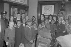 Children, adults, and Baltimore City police officer posing inside unidentified theater, circa 1960. Paul Henderson, HEN.00.B1-025.