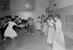 Young men and women dancing inside gymnasium, circa 1953. Paul Henderson, HEN.00.B1-099.