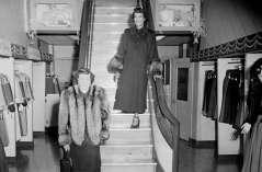 Two unidentified women in coats inside clothing store, circa 1949. Paul Henderson, HEN.00.B1-103.