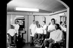 Interior of barbershop with customers and barbers, circa 1949. Paul Henderson, HEN.00.B1-109.