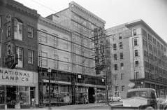 Shows National Lamp Company, Stanley's Furniture, Amoco Gas Station, Henry W. Checket and Company Clothing and Furniture store, pedestrians, automobiles. Scaffolding on Stanley's Furniture. Eutaw Street and Mulberry Street, Baltimore, circa 1952. Paul Henderson, HEN.00.B1-145.