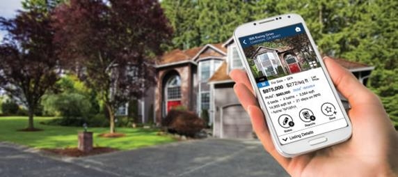 Hand holding an iPhone while looking up a house
