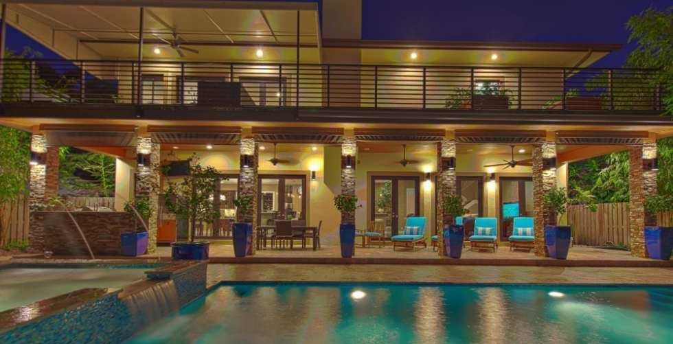 Nighttime View Of A Modern Two-story House With A Pool
