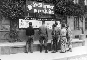"Germans read Streicher's propaganda. Sign reads ""With The Sturmer Against the Jews."" Source: Bundesarchiv via Wikimedia Commons."