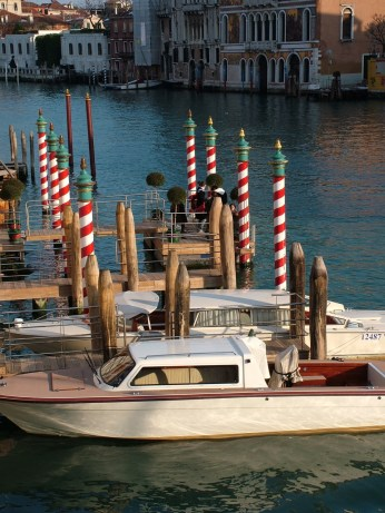 Venetian motor launches tied up next to poles on Grand Canal © Henry Hyde