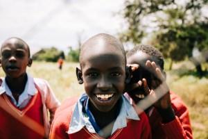 Happy but poor children looking through a fence - Bennett Tobias