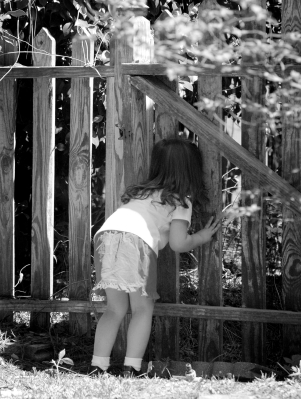 Little girl peeking through fence