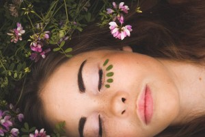 Beautiful Woman With Her laying Inside a Flower Field with Her Eyes Closed